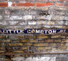 Little Compton Street's subterranean street sign viewed through a street grate
